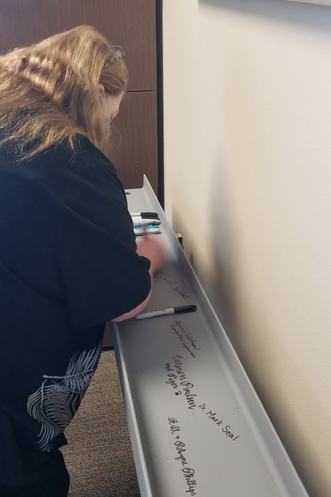 Photo of Cathy Christianson signing the beam