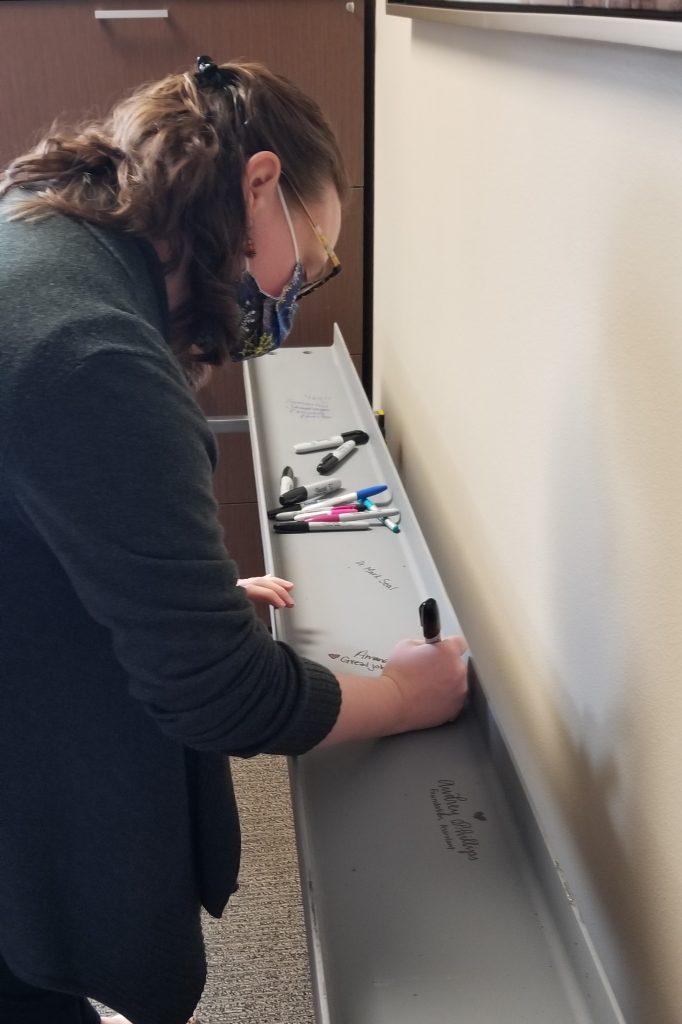 Photo of Amanda Cunningham signing the beam