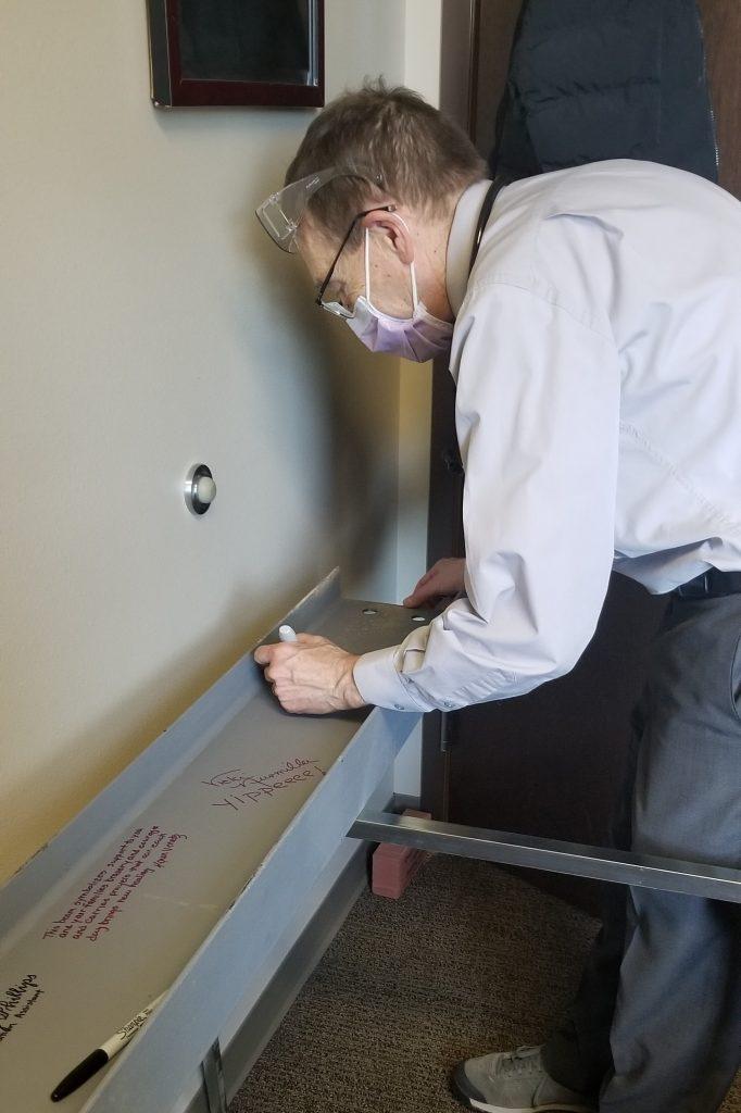 Photo of Dr. Bob Maynard signing the beam