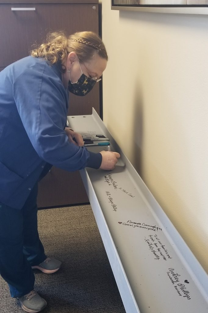 Photo of Dianna Wichman signing the beam